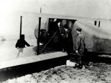 Passengers boarding biplane at Central and Roanoke