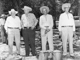 Group of older ranchers standing in front of a dutch oven and coffee pots