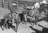 Two cowboys on saddled horses in corral