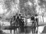 Men in suits by a stream