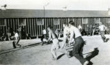 CCC enrollees playing basketball outside barracks