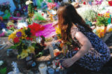 Photo of a girl placing an item among the  tributes at Congresswoman Giffords' office