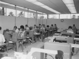 Photograph of workers working on data processing at the Arizona Highway Department offices in...