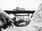 Photograph of a truck crossing a wooden bridge built on an Arizona ranch by Ted Spurlock