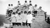 Photograph of Navajo children around a hogan on the Navajo Indian Reservation in Apache County...