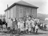 Photograph of students and a teacher at a one room rural Arizona school house