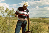 Photograph/color image of Alan Day reading a precipitation meter on the Lazy B Ranch in Arizona
