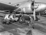 Photograph of four airmen inspecting a plane at Luke Air Force Base in Glendale (Ariz.)