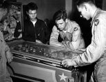 Photograph of airmen playing with a pinball machine at recreational facilities at Luke Air Force...