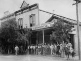 Photograph of a crowd of people near the Old Dominion Commercial Company, a retail store in Globe...