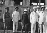 Photograph of Ambassador George  and a group of people near a train in Siam.