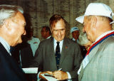 Photograph/color image of retired Naval Officer Louis Conter and Frank Campbell visiting with...