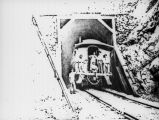 Photograph of a railroad caboose entering a cave