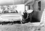 Photograph of Charles Wright digging out his car, damaged by a flood on his farm in Eloy (Ariz.)