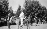 Photograph of Arizona Governor George  riding a burro in a parade in Flagstaff (Ariz.)