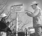 Photograph of a posed image of a trespassing sign and men with guns in Ruby (Ariz.)