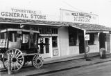 Photograph of a carriage and stores on a street in Tombstone (Ariz.).