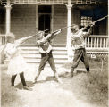 Photograph of three children shooting rifles in a yard in Phoenix (Ariz.).