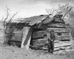 Photograph of Ms. Ola Young, postmaster, near a dilapidating log cabin in Young (Ariz.)