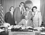 Photograph of Governor Ernest McFarland signing legislation relating to opticians at the Capitol...