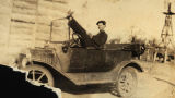 Photograph of a young man sitting in an automobile on a ranch, possibly in Scottsdale (Ariz.).