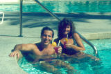 Photograph/color image of a couple drinking alcoholic drinks in a resort swimming pool in Arizona.