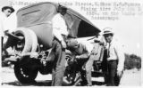 Photograph of staff repairing the tire on the car of Governor George W.P.  in Yavapai County...