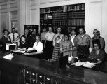 Photograph of the staff gathered behind the reference desk of the Arizona State Library in Phoenix...