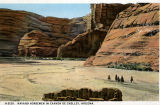 Photograph/colorized postcard of Native Americans riding horses in Canyon de Chelly (Ariz.)