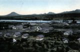Photograph/colorized postcard of Granite Reef Dam and the construction camps surrounding it, in...