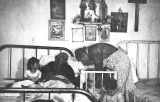 Photograph of a woman tending a bed-ridden female patient as part of a Works Progress...