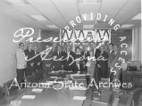 Photograph of a group of legislators meeting with officials of the Arizona Highway Department in...