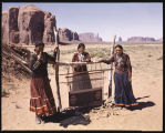 Loom in the Desert. With mighty rock formations in Monument Valley, Arizona as a background, three...