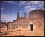 The Three Sisters Formation in Monument Valley, Arizona. Beyond an abandoned Navajo hogan the...