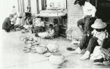 Native American artisans selling wares in front of the Winslow Harvey House, 1908