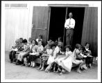 Teacher Henry Howe with students at the Page Accomodation School [constructed title], 1957.
